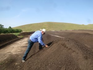 Organic almond grower Ward Burroughs produces compost for improving soil health.
